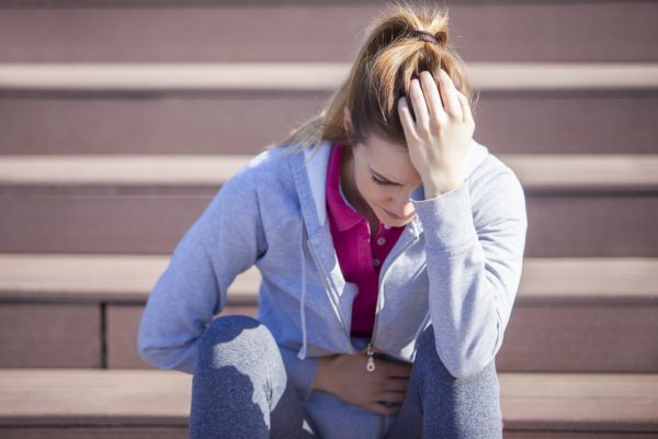 Young woman with abdominal pain after sitting on the steps of recreational running