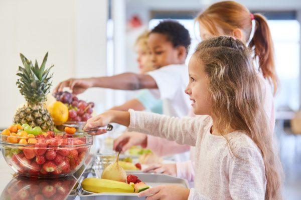 Kinder am Obst Büffet der Grundschule